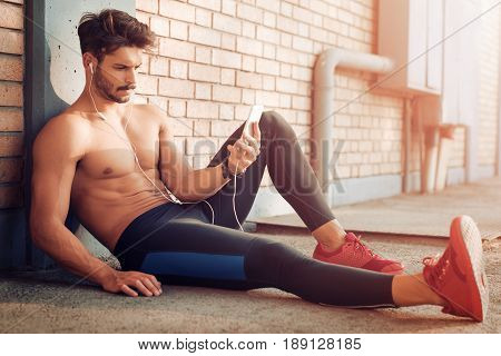 Young man listening to music on a smart phone.He is listening music on smart phone in the city.