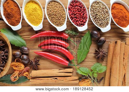 Spices in ceramic containers on wooden background. Food and cuisine ingradients.