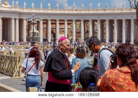 Rome, Italy - May 18, 2017: Bishop and tourists at St. Peter's Square in Vatican. St. Peter's Square is  most visited place in Rome.