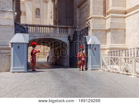 Rome, Italy - May 18, 2017: The Swiss guardsman in parade uniform on the post in front of the Vatican palace in Rome. The Vatican is the most visited place for tourists.