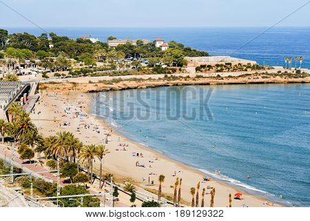 TARRAGONA, SPAIN - MAY 28, 2017: Sunbathers at Miracle Beach in Tarragona, Spain. The city, in the famous Costa Daurada area, has several urban beaches like this, frequented mostly by local