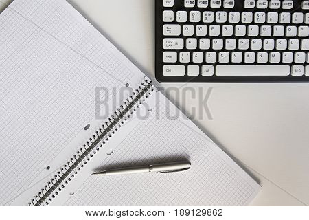 Open Notebook In A Cage With Pen Near The Keyboard On The Desktop