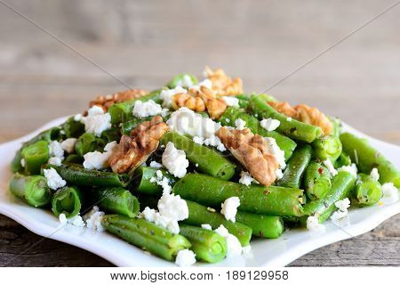 Spicy green bean salad recipe. Baked green beans salad with cottage cheese, crunchy walnuts, garlic and spices on a plate and a vintage background. Simple vegetarian bean salad. Closeup