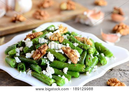 Green bean salad recipe. Delicious green beans salad with cottage cheese, walnuts, garlic and spices on a plate and on a vintage wooden table. Healthy warm salad idea. Closeup