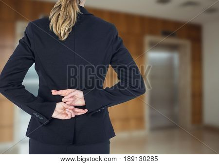 Digital composite of Business woman arriving to the new office with his fingers crossed