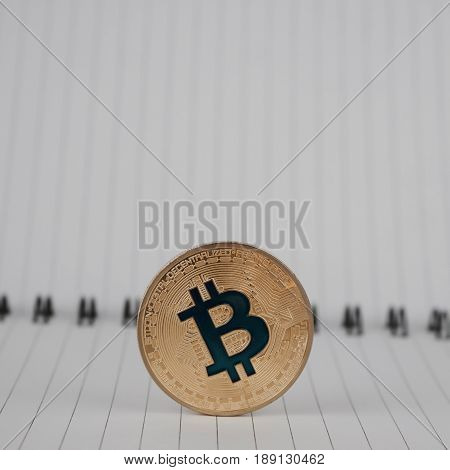 Cryptocurrency physical gold bitcoin coin in notebook