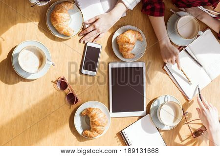 Overhead View Of Young Women Sitting At Coffee Break With Digital Devices, Business Lunch