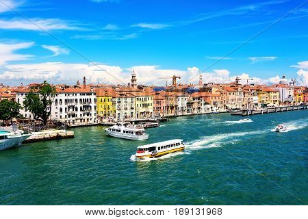 Lagoon in Venice Italy with water taxi's and coastline architecture