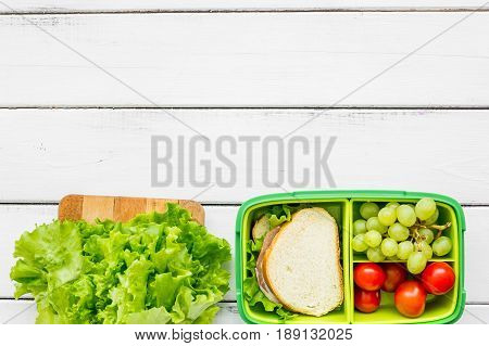 healthy food in lunchbox for dinner at school on white wooden table background top view mockup