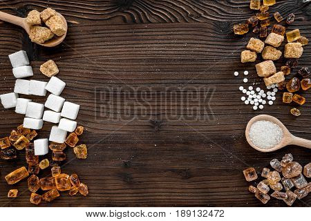 lumps of sugar in spoons on wooden kitchen table background top view space for text
