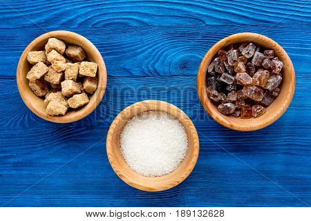 sugar in lumps for sweet food cooking on kitchen blue table background top view