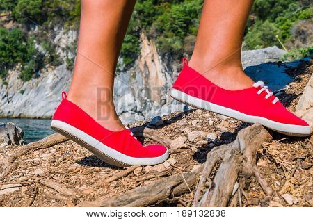 Close up of a tourist girl feet wearing red shoes hiking on cefalonia island, mediterranean, greece.