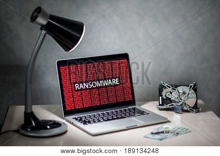 laptop computer screen with ransomware attack alert in red digital binary background with hard disk drive lock Cyber attack concept