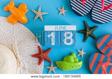 June 18th. Image of june 18 calendar on blue background with summer beach, traveler outfit and accessories. Summer day.