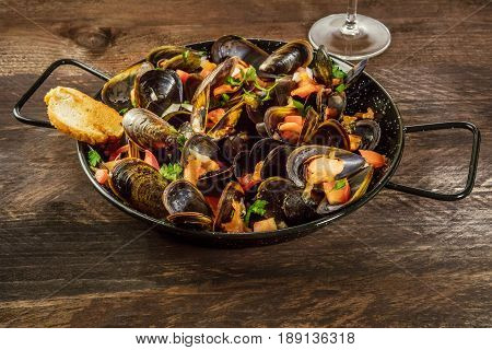 A skillet of marinara mussels on a dark rustic background with a piece of bread, a glass of wine, and a place for text