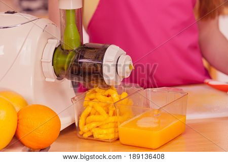 Woman young housewife in kitchen making fresh orange juice in juicer machine preparing nutritious vitamin packed drink. Healthy eating vegetarian food dieting and people concept
