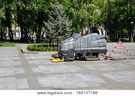Kremenchug, Ukraine - May 5, 2017: Street sweeper machine cleaning walkways in the park