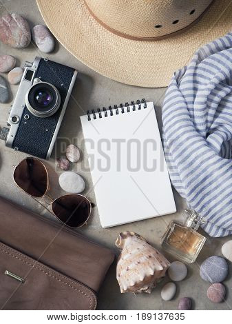 Flat lay, top view traveler's table desk floor. Workspace with notebook, diary, straw hat and sun glasses, vintage camera striped silk scarf, handbag, perfume bottle, pebbles with shell