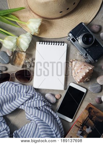 Flat lay, top view traveler's table desk floor. Workspace with notebook, diary, straw hat and sun glasses, vintage camera striped silk scarf, white flowers tulips, perfume bottle, pebbles with shell, book