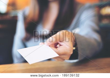 A beautiful Asian business woman holding and giving empty business card in modern loft cafe