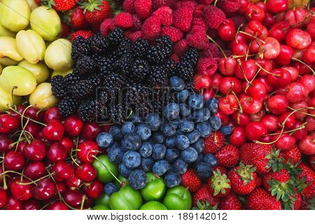 Assorted fresh bright and juicy berries - blueberries, strawberries, raspberries, cherries, plums. A colorful harvest of summer berries and fruits. Top view and soft focus.