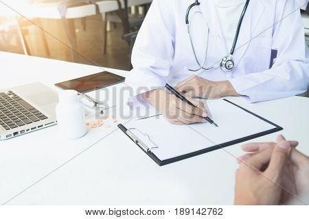 Health care and Medical concept patient listening intently to a female doctor explaining patient symptoms or asking a question as they discuss paperwork together in a consultation.