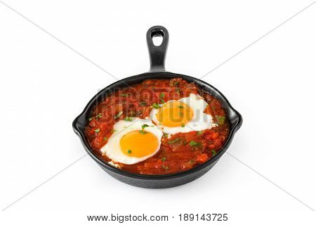 Mexican breakfast: Huevos rancheros in iron frying pan isolated on white background