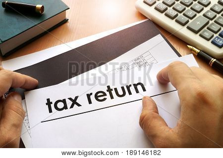 Hands holding documents with title tax return.