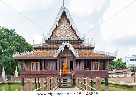 Yasothon Thailand - May 2017: Thai Buddhist monk standing in front of Ho Trai - Traditional Thai-style building used as a library that houses Buddhist scriptures (Tripitaka) located at Wat Mahathat Temple