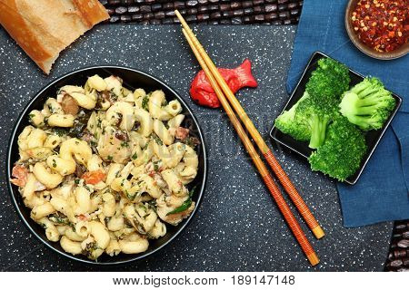 Chicken Alfredo and Broccoli Meal at table setting with chopsticks, bread and crushed red pepper.