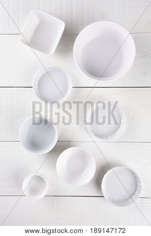 Top view of a group of ceramic ramekins on a rustic white wood table.