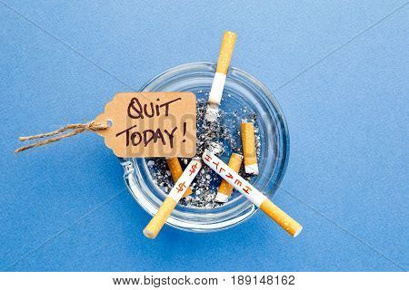 Stop Smoking - Quit Today - with cigarettes, ashtray and handwritten tag on blue background