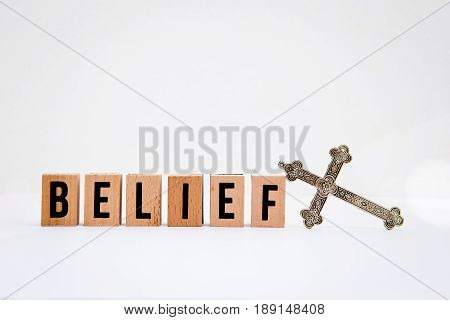 Belief in wooden block letters with silver cross on white background