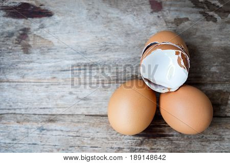 Two fresh eggs and egg shell on wooden background.