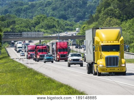 A yellow semi leads a packed line of traffic down an interstate in Tennessee. Heat rising from the pavement gives a shimmering effect to vehicles and forest in the background