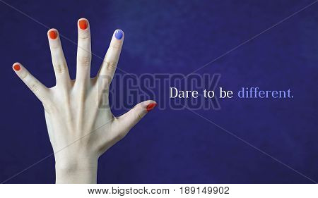 Dare to be different. Originality and creativity concept with blue background. One different nail color in finger in caucasian hand. Red and blue painted fingernails. Stand out from the crowd.