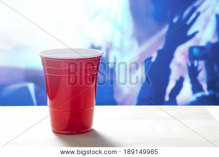 Plastic red party cup on a table. Nightclub full of people dancing on the dance floor in the background. Disco lighting. Perfect for marketing and promotion for events or college fest.