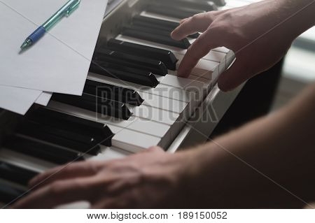 Piano lessons, coaching, teaching or training concept. Talented pianist showing example with digital music instrument. Intimate and cinematic view of male hands on keys. Man playing keyboard.