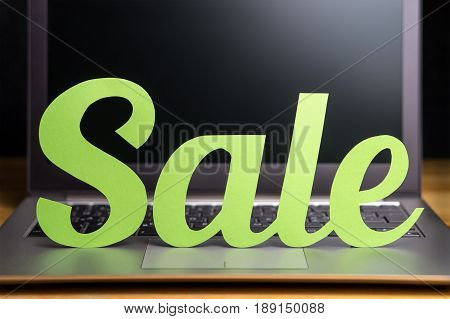 Online store sale ad. Promotion and marketing banner for an internet shop. Light green cardboard letters cut from cardboard paper on laptop computer. Vibrant and cathcy shopping and e-commerce design.