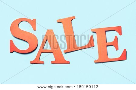 Sale banner. Colourful craft banner for marketing special discount prices or campaign offer. Letters cut from cardboard paper on a light blue background. Hand made red orange text for advertising.