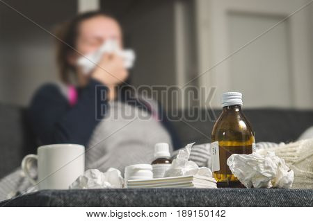 Sick woman sneezing to tissue. Medicine, hot beverage and dirty paper towels in front. Girl caught cold. Cough syrup and handkerchiefs on table. Very ill person feeling bad and having fever.