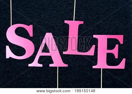 Fuchsia sale text on dark background. Pink red letters cut from cardboard paper on wooden stick. Distinct design for promoting online shop discount or marketing special campaign offer.