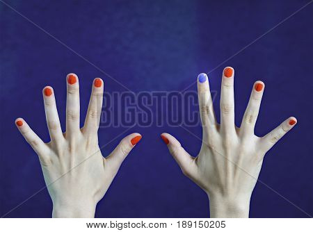 One different nail color in finger in caucasian hands. Red and blue painted fingernails. Stand out from the crowd, originality and creativity concept with blue background. Dare to be different.
