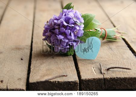 Merci written on tag and a bouquet of violets