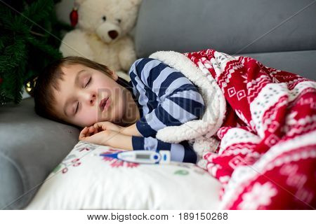 Sick little child boy with high fever sleeping on the couch at home lots of medicine on the table