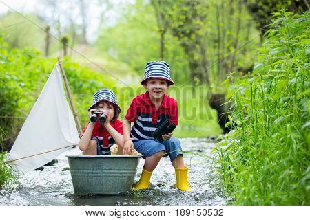 Cute Children, Boys, Playing With Boat And Ducks On A Little River