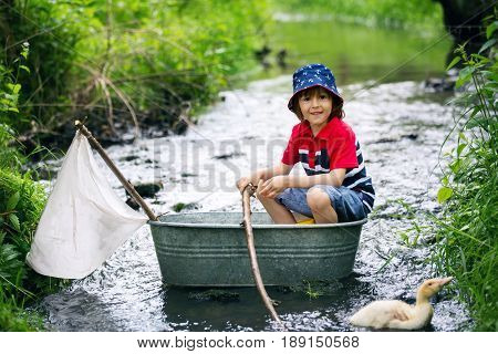Cute child boy playing with boat and ducks on a little river sailing and boating. Kid having fun childhood happiness concept