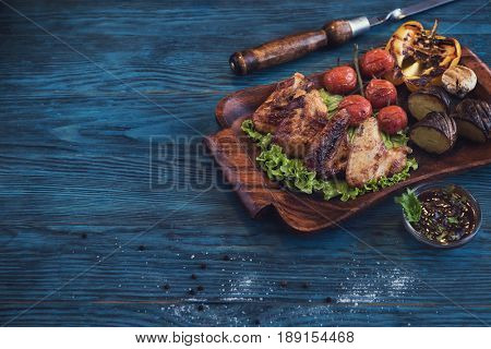 Grilled chicken meat with vegetable on a blue wooden background