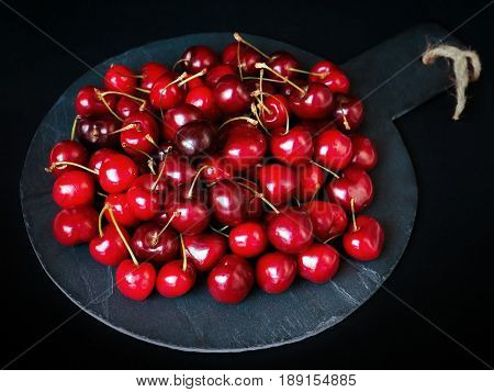 Mix of ripe cherries prepared on round-shaped stone. Bright red fruit on a black background.