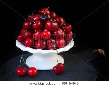 Tasty ripe cherries prepared on white porcelain bowl brilliant red fruit on a black background.